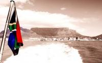 The South African flag blowing in front of Table Mountain, onboard the Sikhululekile ferry, which transports visitors to Robben Island from Cape Town harbour. (Image: Witstinkhout: Wikimedia Commons)