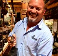 Here Mornay Beukes, Manager of ATKV Hartenbos, barely manages to hold one of the heavy irons dating back to the 1800's.