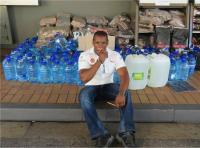 """Armstrong Bova at the Shell service station in Knysna had to """"keep track"""" last week when hundreds of litres water were donated by residents and businesses of Sedgefield and Knysna (Photo: Knysna-Plett Herald)"""
